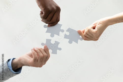 Obraz Close up bottom view diverse colleagues holding white pieces of puzzle, finding searching business solution, solving problems together, employees engaged in team building activity, support and help - fototapety do salonu