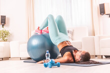 Young Girl Holds Legs On A Fitness Ball Lifting Her Whole Body With Elbows On The Floor. Home Workout Using A Mat, Dumbbells And A Swiss Ball