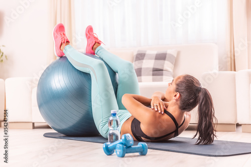 Home workout of a fitness girl, exercising abs with feet on a fit ball Slika na platnu