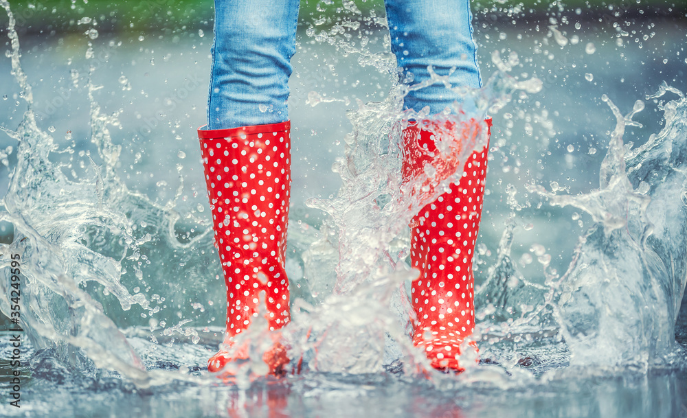Fototapeta Detail of a moment when red polka dot rain boots jumped into a puddle of water, splashing all around