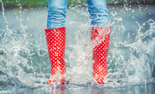 Detail Of A Moment When Red Polka Dot Rain Boots Jumped Into A Puddle Of Water, Splashing All Around