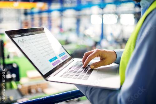 Unrecognizable technician or engineer with laptop standing in industrial factory Fototapeta