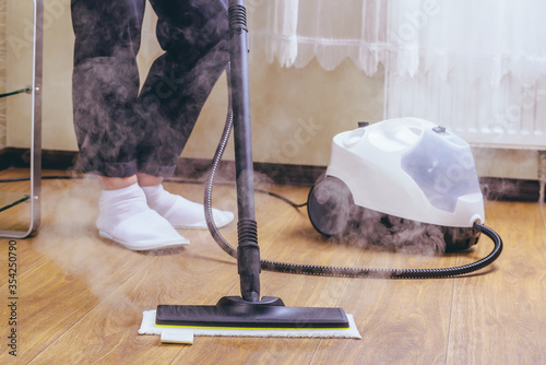 The woman washes the floor in the room with a white steam cleaner, a wet high-pressure steam Canvas Print