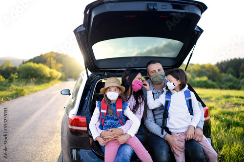 Family with two small daughters on trip outdoors in nature, wearing face masks Wallpaper Mural