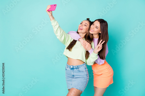 Obraz Photo of two pretty cheerful ladies best friends hold telephone take selfies showing v-sign symbol wear cropped sweaters naked belly short skirts isolated pastel teal color background - fototapety do salonu