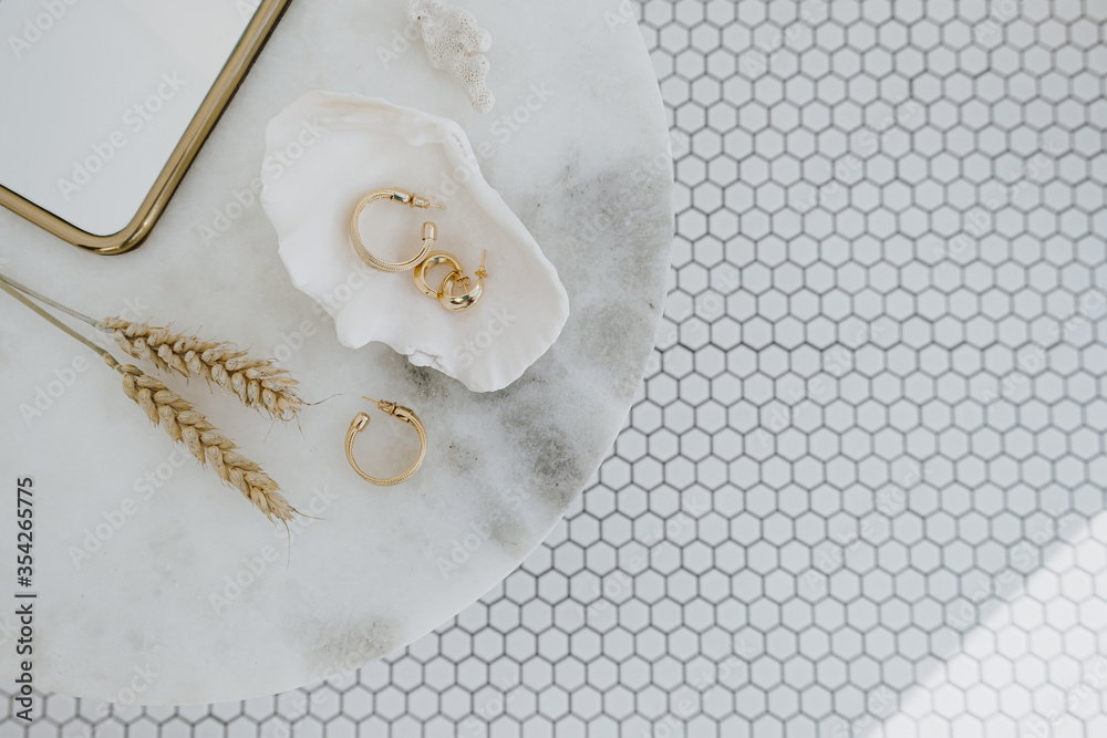 Fototapeta Minimal fashion composition with golden earrings in seashell on marble table with mirror and wheat stalks. Flat lay, top view bijouterie / jewelry concept on mosaic tile background.