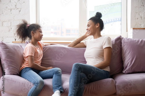 Photo African family spend time at home mother sitting on couch with pre-teen daughter women talking smiling enjoy pleasant honest conversation