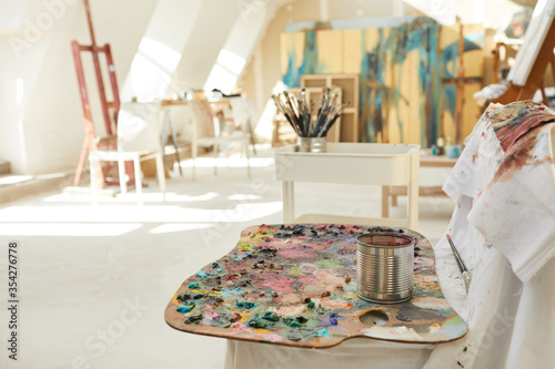 Obraz Background image of empty art studio lit by sunlight, focus on artist pallet in foreground, copy space - fototapety do salonu