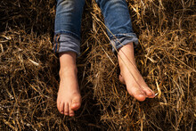 Feet Of A Small Child In The Hay