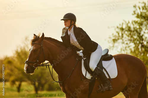 Girl equestrian rider riding a beautiful horse  in the rays of the setting sun Wallpaper Mural