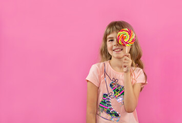A little girl is looking through a lollipop. Little girl on a pink background. Happy child with candy in hands. A little girl holds in her hands a multi-colored candy on a stick.Fashion look.