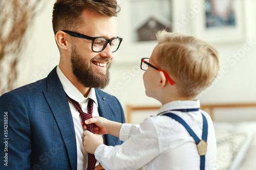 Fotografiet happy son helps father tie a necktie at home.