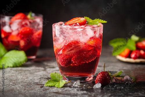 Fototapeta Refreshing summer drink with strawberry slices in glasses on dark background obraz