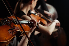 Cropped View Of Female Professional Musicians Playing On Violins On Dark Stage, Selective Focus
