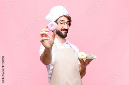 Fotografia young crazy baker man confectionery concept against pink wall