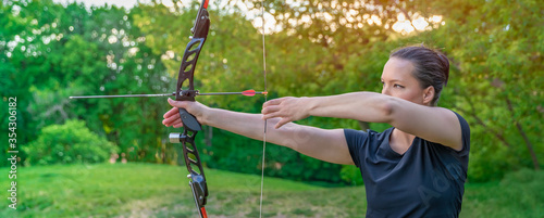 Billede på lærred archery in nature, young woman aiming an arrow at a target