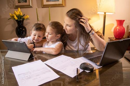 mamma con figli giocano con i computer seduti al tavolo del salone Tapéta, Fotótapéta