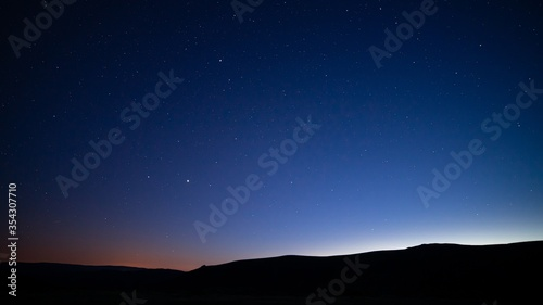 Silhouettes of hills under a starry sky at night - perfect for wallpapers and ba Canvas Print
