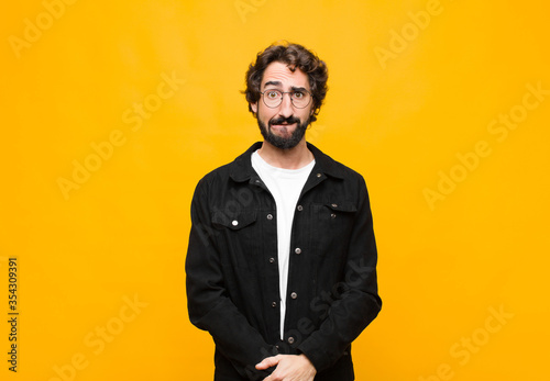 Fototapeta young crazy handsome man looking puzzled and confused, biting lip with a nervous gesture, not knowing the answer to the problem against orange wall obraz