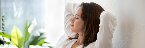 Beautiful 30s woman closed eyes put hands behind head relaxing on comfortable sofa in cozy warm light living room with houseplants, no stress concept, horizontal photo banner for website header design