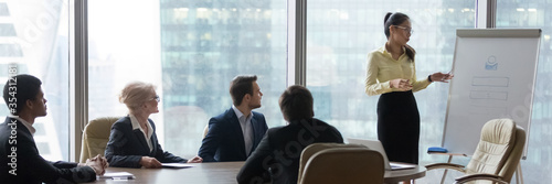Obraz Asian businesswoman coach makes presentation for multi-ethnic international company staff using flip chart. Corporate training, negotiations concept. Horizontal photo banner for website header design - fototapety do salonu