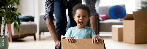 Tablou Canvas African dad play with excited toddler son riding seated inside of box in moving day at new home, little kid enjoy game with daddy, relocation concept