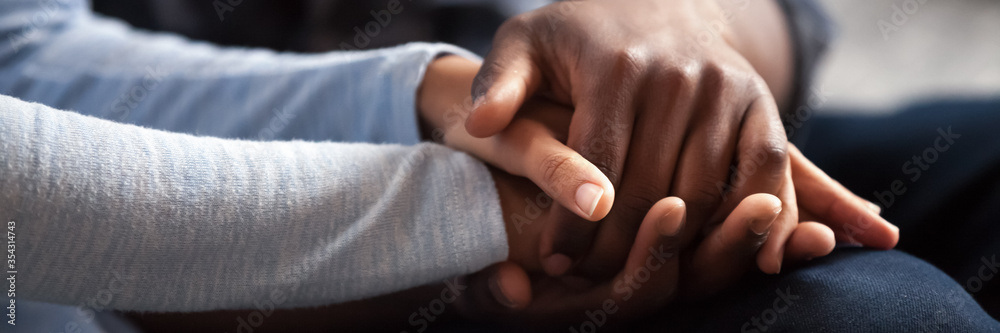 Fototapeta Close up photo african couple in love, woman man holding hands. Gesture of sincere feelings, compassion, apology, reliable friend, share pain or happiness. Horizontal banner for website header design