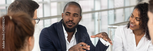 Obraz Multi ethnic employees involved in corporate training in boardroom, african team leader company boss business coach leading seminar activity concept. Horizontal photo banner for website header design - fototapety do salonu