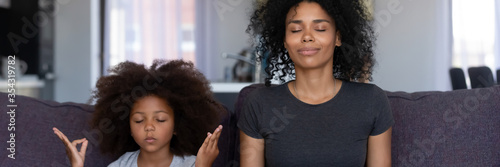 Obraz Calm African mother her funny little daughter sit on couch do meditation practice together at home. No stress, teach kid healthy life habits concept. Horizontal photo banner for website header design - fototapety do salonu