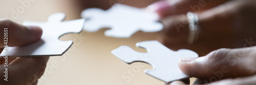 Fotografía Close up photo hands of multi ethnic people hold diverse pieces of puzzle, team assembling jigsaw joining fragments, teamwork, search find solution concept