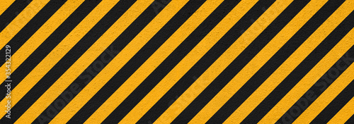 Photo banner of plaster wall with black and yellow restricted area marking