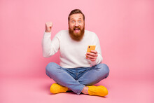 Ful Length Photo Delighted Guy Sit Floor Legs Crossed Use Smartphone Blogging Win Social Media Lottery Raise Fists Scream Yes Wear White Jumper Denim Jeans Isolated Pastel Color Background