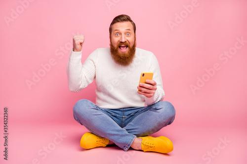 Fotografía Ful length photo delighted guy sit floor legs crossed use smartphone blogging wi