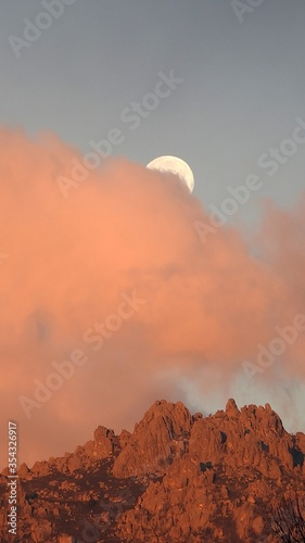 Vertical shot of the orange clouds covering moon and rocks