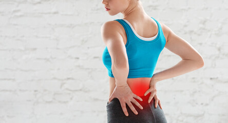 Cropped view of young woman feeling pain in her lower back after workout at gym, copy space