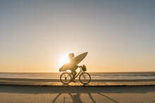 Surfer Riding A Bicycle During...
