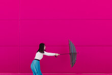 Young Woman Holding Umbrella In Front Of A Pink Wall