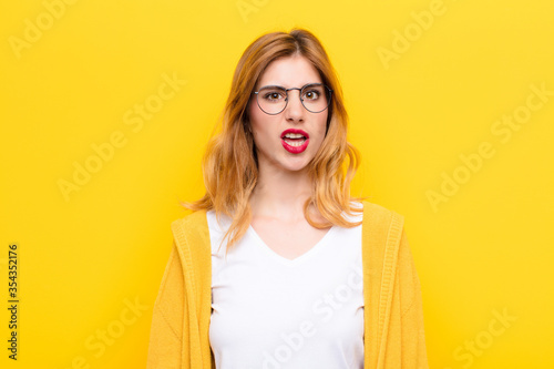 Fototapeta young pretty blonde woman feeling puzzled and confused, with a dumb, stunned exp