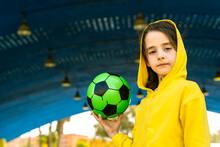 Portrait Of Little Girl Wearing Yellow Hooded Jacket Holding Soccer Ball