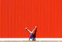 Young Man Doing A Handstand At A Red Wall