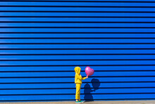 Little Girl Wearing Yellow Tracksuit  Standing With Pink Balloon In Front Of Blue Background