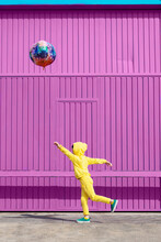 Children Dressed In Yellow Standing In  Front Of Purple Garage Door Holding Balloon