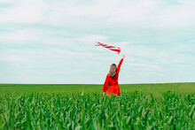 Back View Of Woman Wearing Red Dress Holding Windsock On A Field