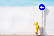 Girl With Her Cuddly Toy At Traffic Sign, Direction Left, In Front Of A White Wall