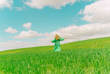 Rear View Of Woman In Green Dress Walking In Field