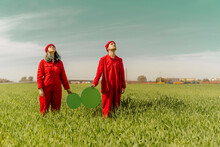 Young Couple Wearing Red Overalls  Standing On A Field With Two Green Circles Looking Up