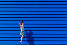 Little Girl With Colourful Butterfly Wings Jumping In The Air In Front Of Blue Background
