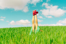 Young Woman Wearing Red Shoes Relaxing On A Field With Legs In The Air