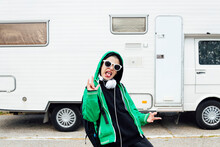 Portrait Of Boy Standing In Front Of Camper Sticking Out Tongue And Showing Rock And Roll Sign