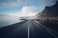 Iceland, Back View Of Woman With Backpack Walking On Median Strip Of Country Road